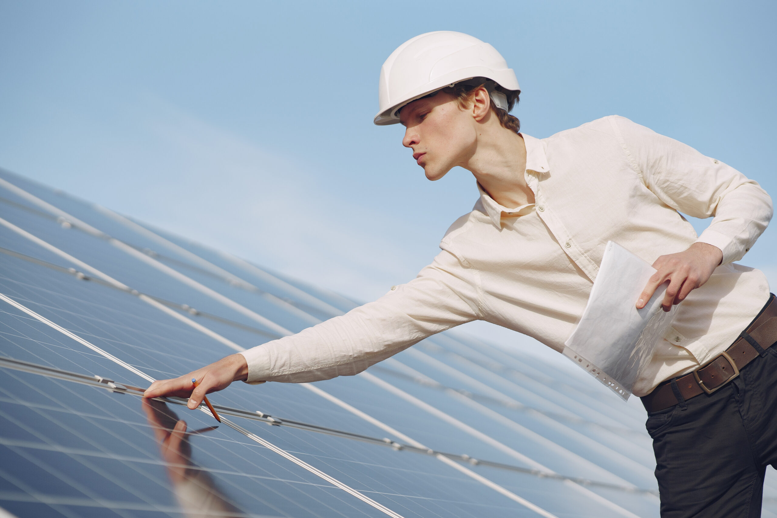 Portrait of client in white helmet at solar power station. Man in business suit.